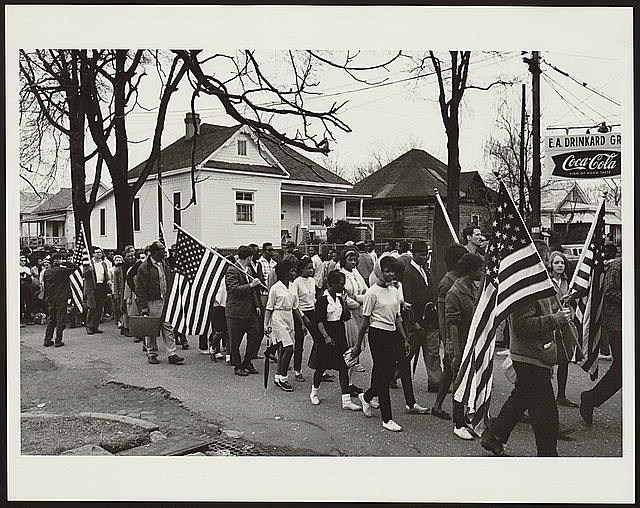 Participants, some carrying American flags, marching in the civil rights march from Selma to Montgomery, Alabama in 1965. Photo courtesy of the Library of Congress