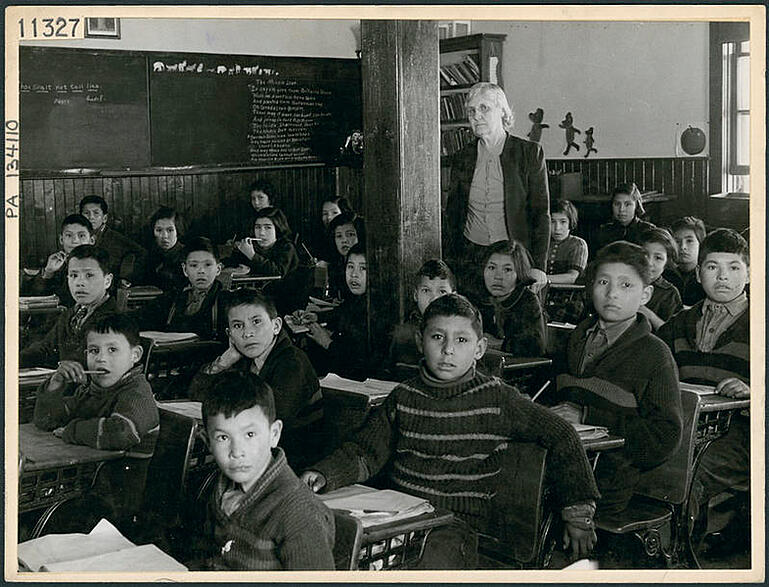 Cree students at their desks with their teacher in a classroom, All Saints Indian Residential School, Lac La Ronge, Saskatchewan, March 1945 (Credit: Bud Glunz / National Film Board of Canada. Photothèque / PA-134110)