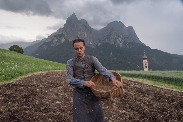 Farmer Franz Jägerstätter planting seeds in St. Radegund, Austria (portrayed by August Diehl in A HIDDEN LIFE). Image Credit: Photo by Reiner Bajo. © 2019 Twentieth Century Fox Film Corporation All Rights Reserved