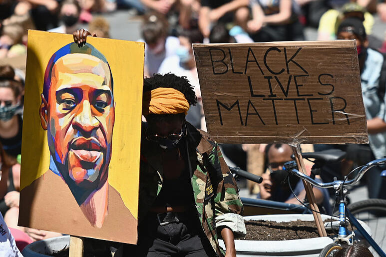 """A protester holding a painting of George Floyd and a sign that reads """"Black Lives Matter"""""""