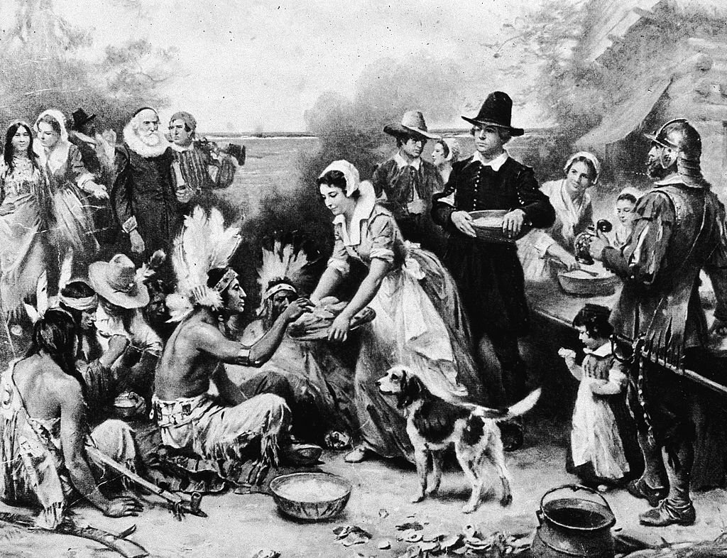 "Pictured above: A black-and-white photo of ""The First Thanksgiving""—an inaccurate portrayal of the first Thanksgiving dinner held in 1621 painted by Jean Leon Gerome Ferris. (Photo by American Stock/Getty Images)"