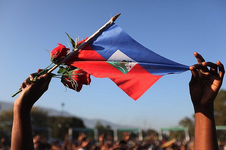 A woman holds a Haitian flag and roses at a church service following the earthquake of January 24, 2010 in Port-au-Prince, Haiti. (Photo by Joe Raedle/Getty Images)