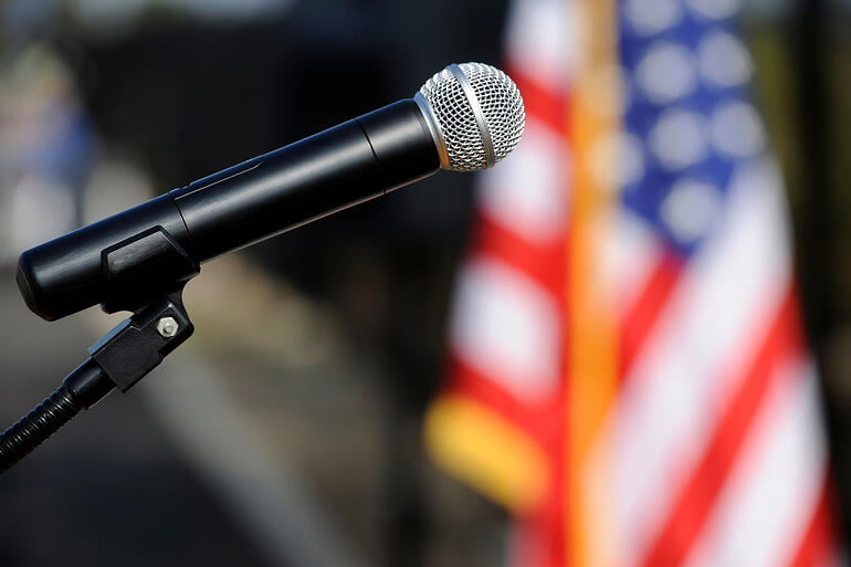 A microphone displayed before an American flag