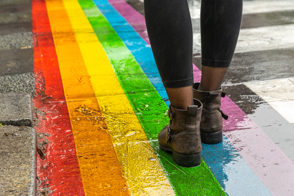 Legs walking across a LGBTQ pride flag painted on the ground