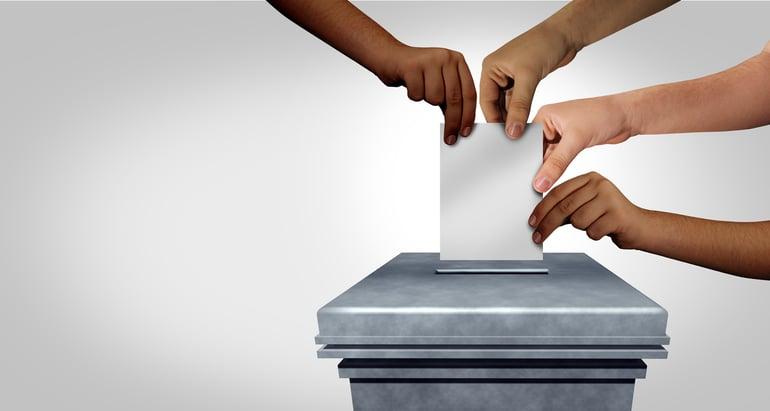 Four hands holding a ballot above a ballot box