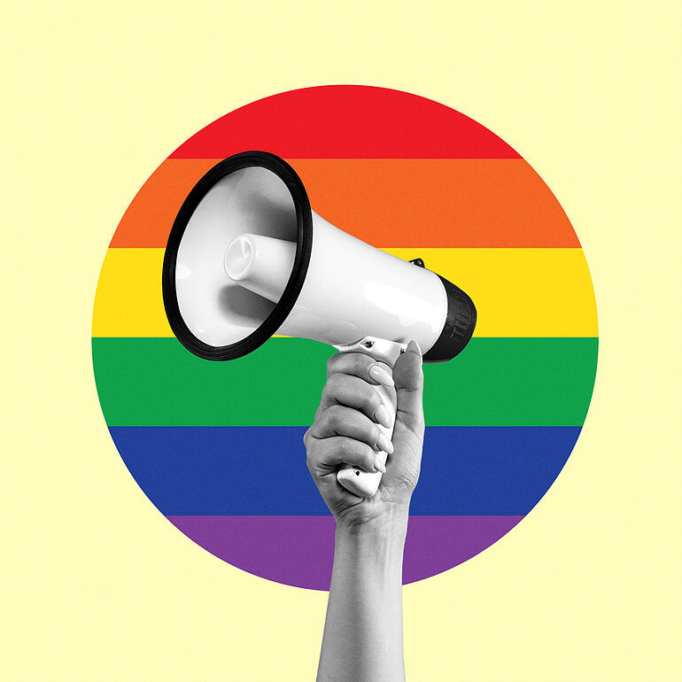 Megaphone with a circular rainbow flag in the background