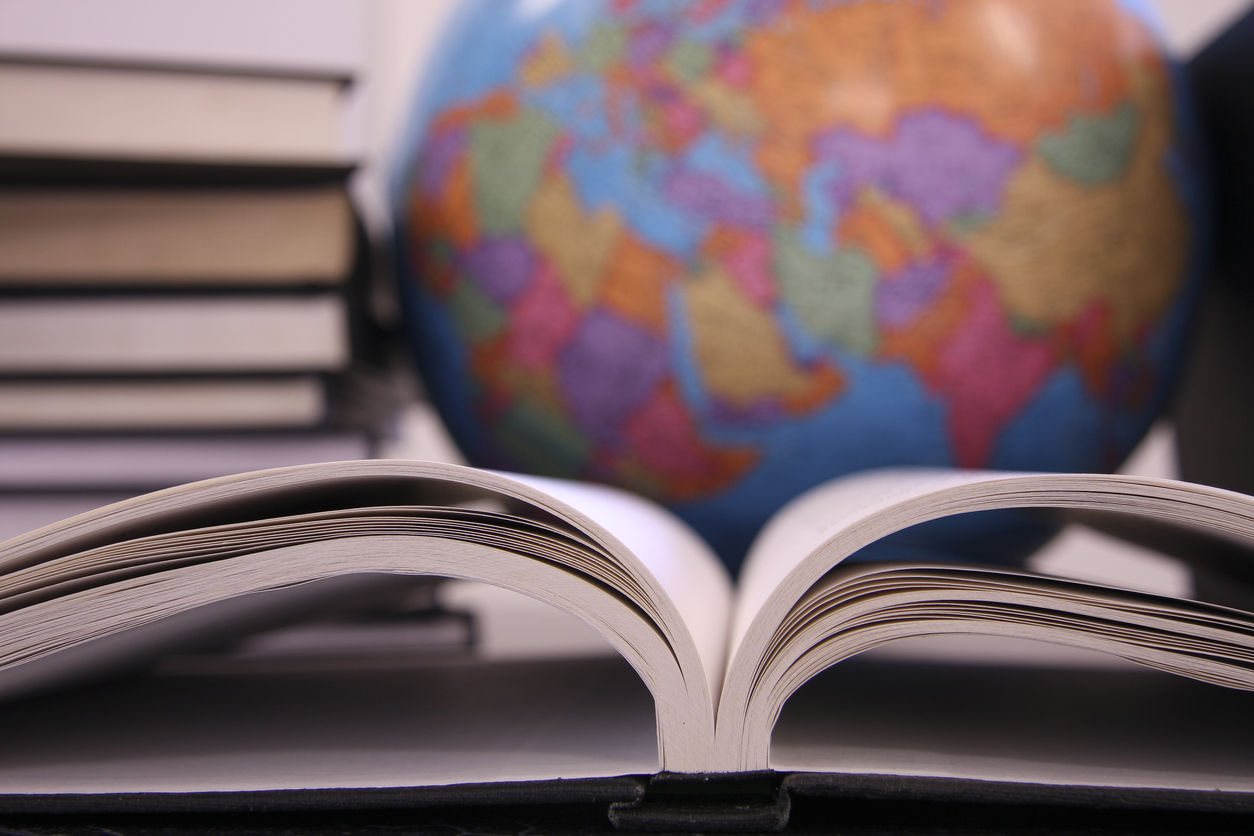 A stack of books, an open book, and a globe